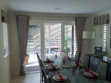 Dining area with curtains on a metal pole and Roman Blinds to the side window